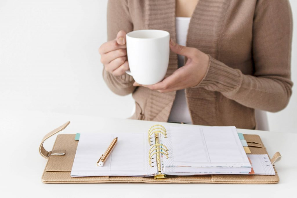 woman with planner and coffee cup