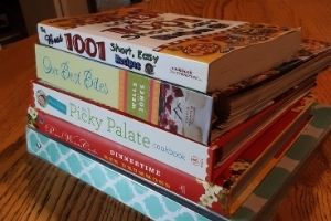Stack of recipe books for meal planning for frugal living tip