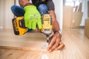 Man using power drill on floor. learn some DIY as part of living frugally